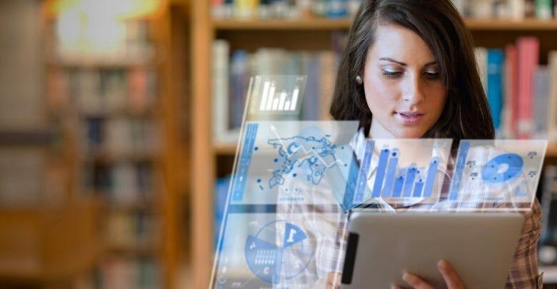 Alumna trabajando en su tablet futurista en la biblioteca