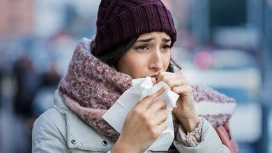 Young woman coughing during winter on street. Girl with cold wearing knitted cap and scarf feeling unwell. Woman feeling sick during for winter and city pollution. Girl with sore throat.
