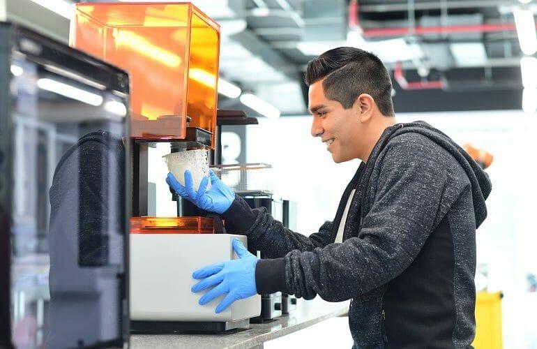 Joven de guantes azules usando una máquina